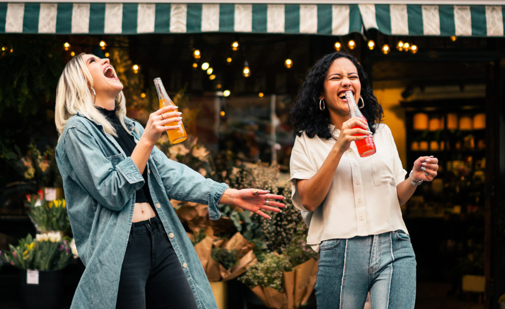 women laughing and drinking soda